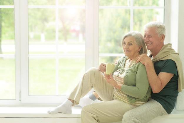 Szczęśliwa starsza para pijąca herbatę siedząca na parapecie w domu
