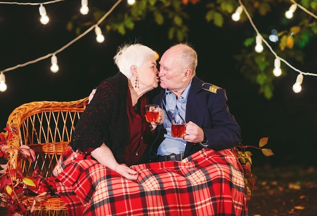 Szczęśliwa starsza para pije herbaty w wieczór obsiadaniu na leżance.
