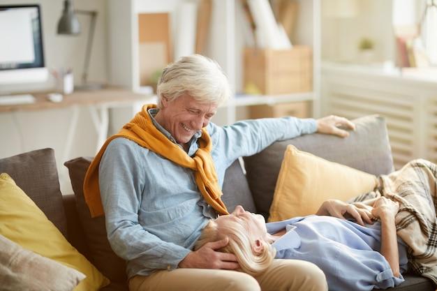 Szczęśliwa starsza para relaksuje na kanapie