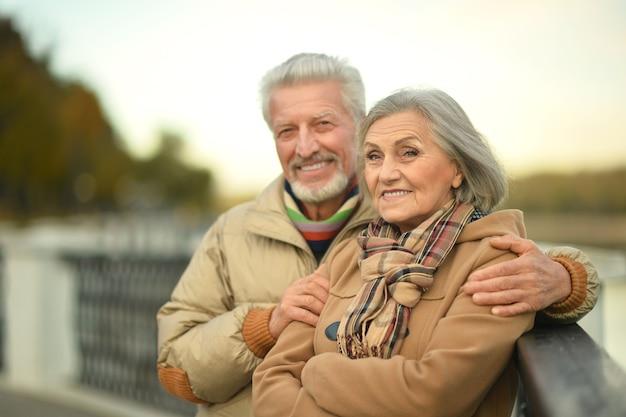 Szczęśliwa starsza para relaksuje się w jesiennym parku w pobliżu rzeki
