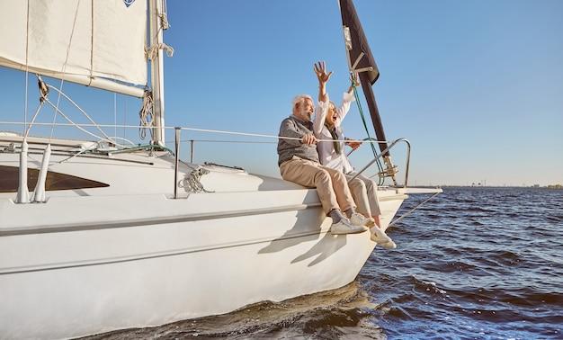Szczęśliwa starsza para siedzi na boku żaglówki na spokojnym błękitnym morzu, ciesząc się widokiem kobiety