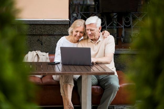 Szczęśliwa starsza para siedzi na ławce na zewnątrz z laptopem