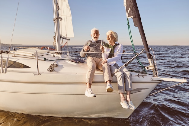 Szczęśliwa starsza para siedzi z boku żaglówki lub pokładu jachtu unoszącego się w morzu mężczyzna i kobieta