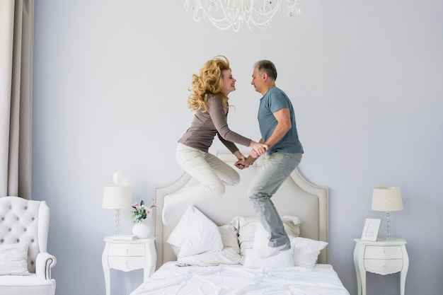 Szczęśliwa starsza para skacze w łóżku