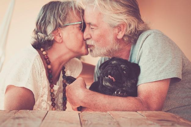 Szczęśliwa starsza para starszych zakochanych całuje się nawzajem i ściska swojego uroczego czarnego psa mopsa