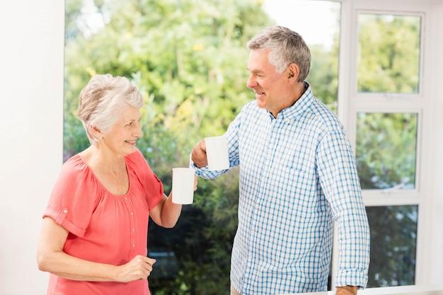 Szczęśliwa starsza para wznosi toast z filiżankami w domu