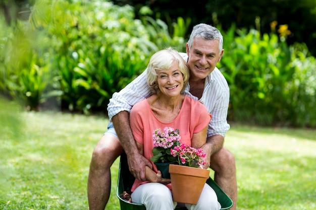 Szczęśliwa starsza para z kwiatów garnkami w jardzie