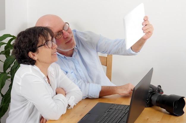 Szczęśliwa starsza para z tblet robi selfie w domu