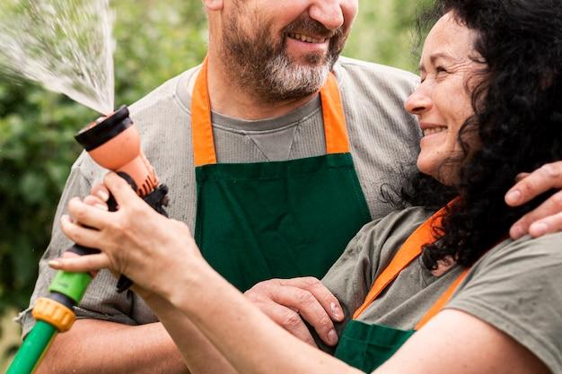 Szczęśliwa starsza para z wodnym wężem elastycznym