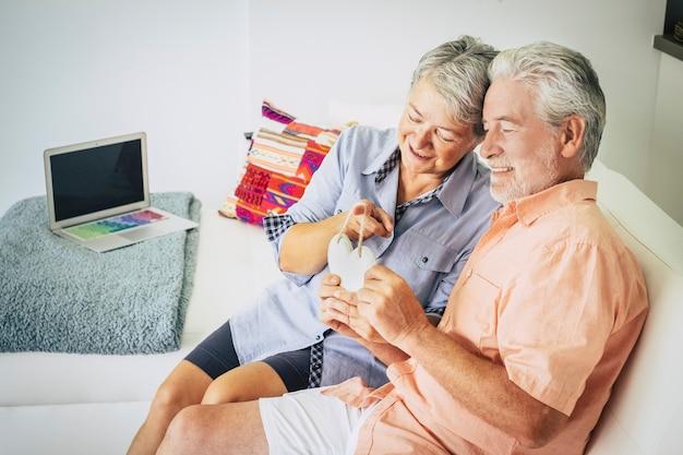Szczęśliwa starsza para zakochanych kaukaskich ludzi siedzi w domu na kanapie i bierze drewniane ręcznie wykonane palenisko na rękach