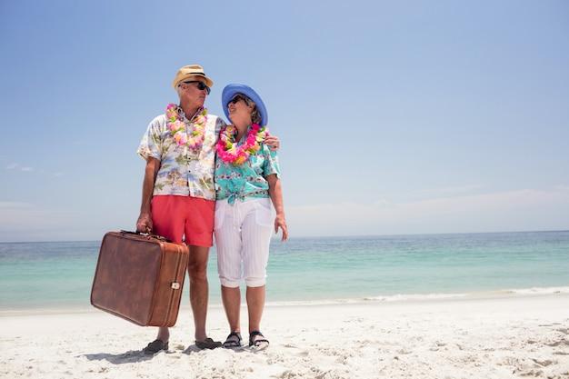 Szczęśliwa starsza pary mienia walizka na plaży