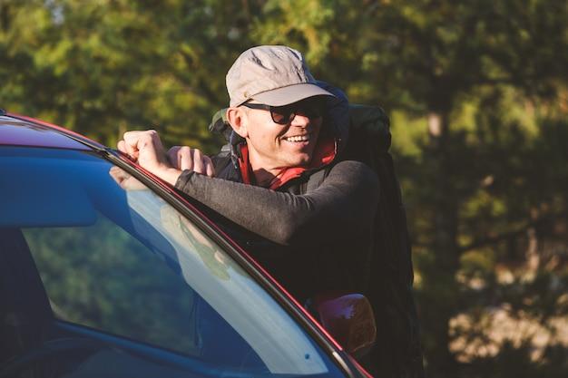 Szczęśliwa starsza poza turystyczna w pobliżu czerwonego samochodu w lesie