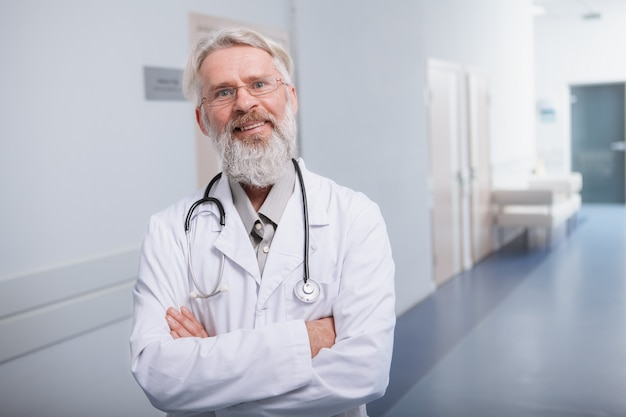 Szczęśliwa starsza samiec lekarka ono uśmiecha się kamera, stoi w korytarzu jego klinika, kopii przestrzeń