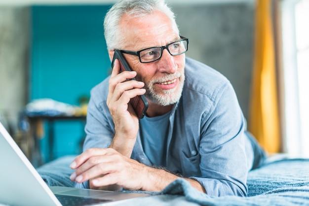 Szczęśliwa starsza samiec opowiada na mądrze telefonie patrzeje daleko od