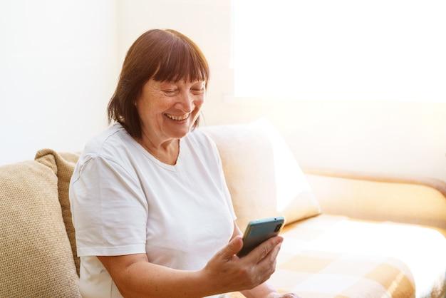 Szczęśliwa starsza starsza kobieta trzymająca smartfona z aplikacją na telefon komórkowy do wideorozmów śmiejąc się podczas watc...