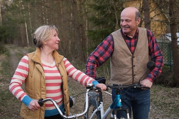 Szczęśliwa starsza starsza para jeździć na rowerze w parku