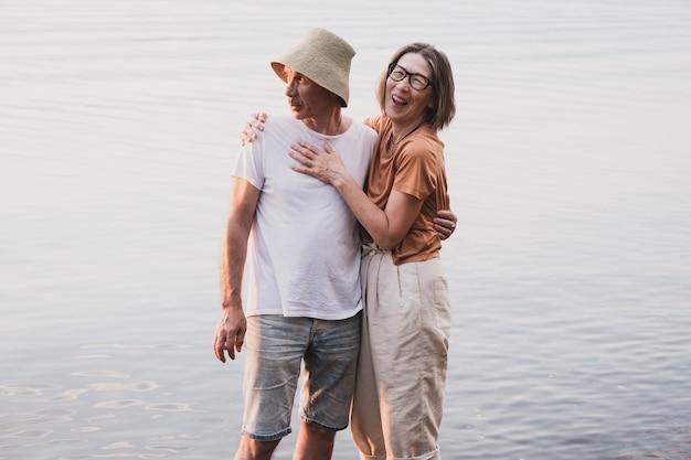 Szczęśliwa starsza zakochana para wielorasowa stojąca w wodzie morza lub rzeki