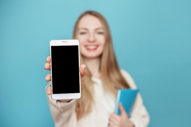 Szczęśliwa studencka dziewczyna pokazuje pusty ekran telefonu komórkowego w aparacie i uśmiecha się, rozmycie dziewczyny. pojedynczo na niebieskiej ścianie w studio. makieta