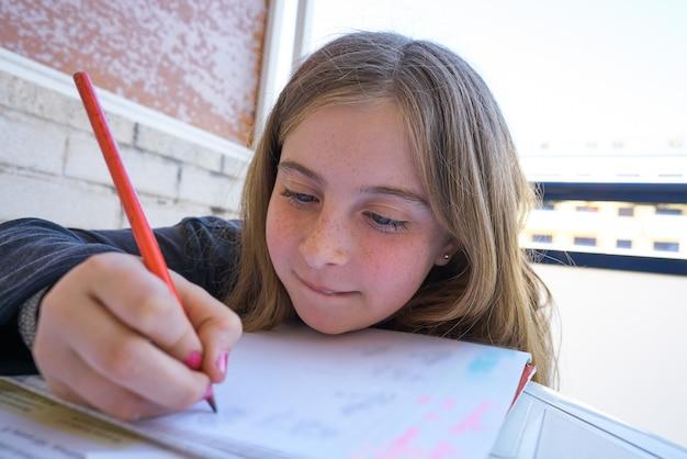 Szczęśliwa studencka dziewczyna robi jej pracie domowej