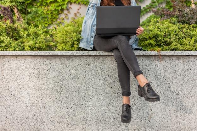 Szczęśliwa studencka kobieta w drelichowej kurtce i szkłach używa laptop podczas gdy siedzący w miasto parku