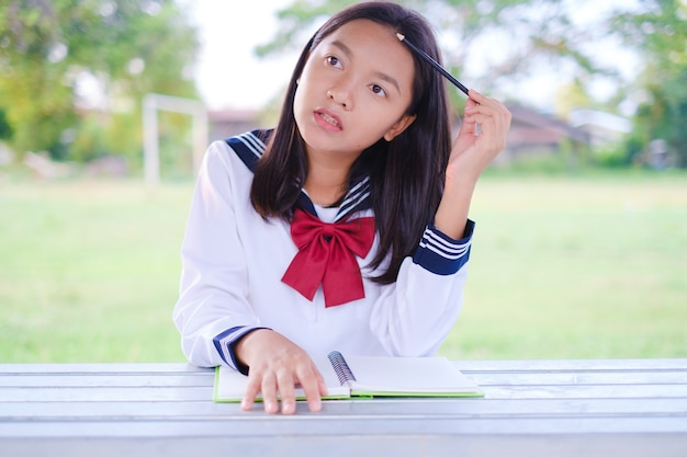 Szczęśliwa studentka z książką rozmieszczającą na zewnątrz w szkole azjatycka dziewczyna