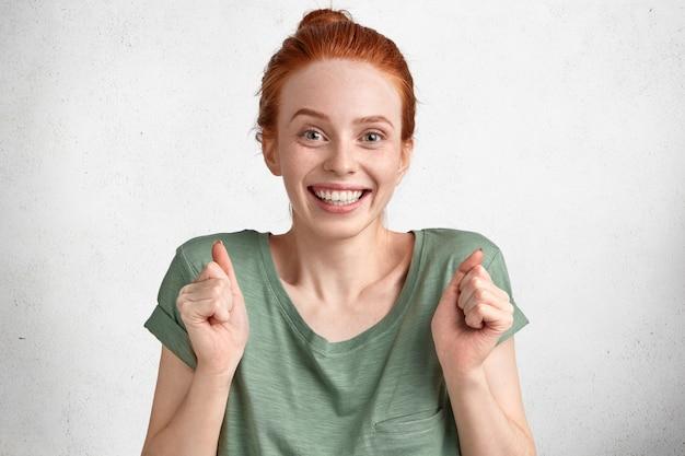 Szczęśliwa studentka z rudymi włosami, raduje się pomyślnie zakończonym projektem, uśmiecha się szeroko i zaciska pięści, podekscytowana pochwałą na białym studio