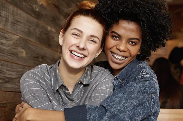 Szczęśliwa stylowa afroamerykańska lesbijka z szelkami i kręconymi włosami trzymająca mocno swoją piękną rudowłosą dziewczynę