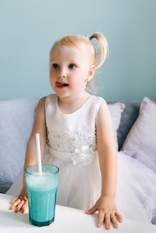 Szczęśliwa stylowa dziewczynka w dziecięcej kawiarni pije milkshake