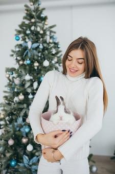 Szczęśliwa, stylowa i piękna dziewczyna otworzyła świąteczne prezenty i otrzymała królika.