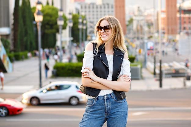 Szczęśliwa stylowa kobieta pozowanie na europejskiej ulicy