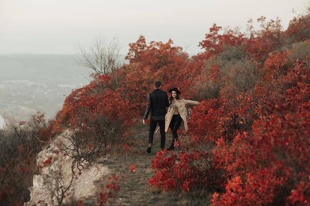 Szczęśliwa stylowa kobieta trzyma mężczyznę za rękę i idąc w dół jesienną górską doliną patrzy i uśmiecha się do swojego chłopaka