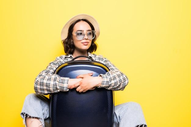 Szczęśliwa stylowa podróżniczka w słomkowym kapeluszu stojącym z torbą na kółkach