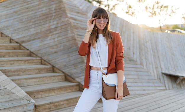 Szczęśliwa stylowa studentka pozowanie w nowoczesnym parku, wesring białe dżinsy, kurtka i t-shirt.