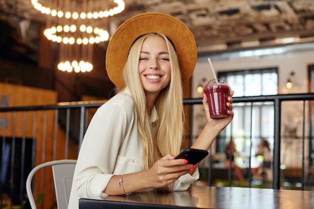 Szczęśliwa stytlish młoda niebieskooka długowłosa kobieta ubrana w szeroki brązowy kapelusz i białą koszulę uśmiecha się radośnie, siedząc nad nowoczesnym wnętrzem kawiarni