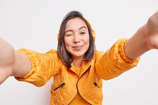 Szczęśliwa szczera azjatka mruga okiem, uśmiecha się zadowolona, wyciąga ręce do przodu, aby zrobić selfie, ciesząc się najlepszymi aplikacjami muzycznymi, nosi bezprzewodowe słuchawki na uszach, nosi pomarańczową kurtkę odizolowaną na białej ścianie