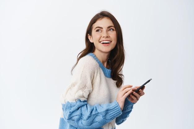 Szczęśliwa szczera dziewczyna z pięknym uśmiechem, korzystająca z aplikacji do czatu na smartfonie i odwracająca głowę do logo przestrzeni kopii, stojąca na białej ścianie