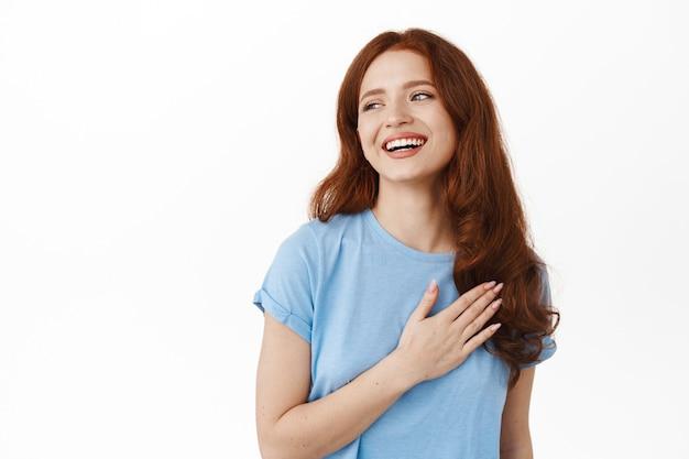 Szczęśliwa szczera rudowłosa dziewczyna śmiejąca się i uśmiechająca naturalnie, trzymająca rękę na sercu i patrząca z boku na coś pięknego i pozytywnego, czytająca logo, stojąca na białym