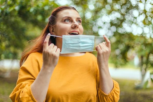 Szczęśliwa szczęśliwa dziewczyna zdejmuje ochronną maskę medyczną
