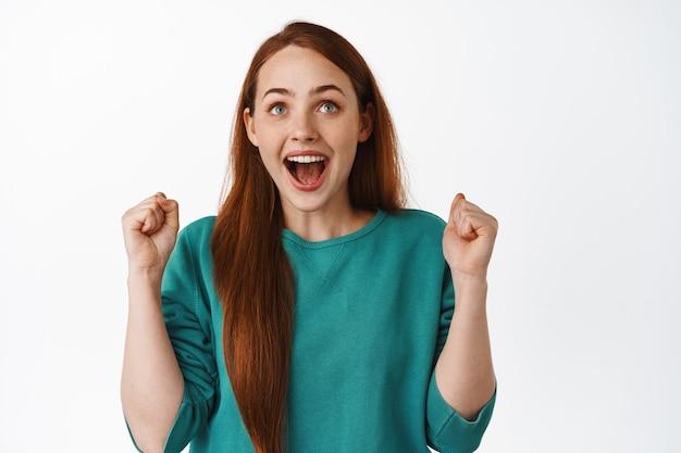 Szczęśliwa szczęśliwa rudowłosa dziewczyna, patrząca w górę i śpiewająca, wygrywająca zakłady, świętująca zwycięstwo, triumfująca z radości, kibicująca drużynie, stojąca na białym