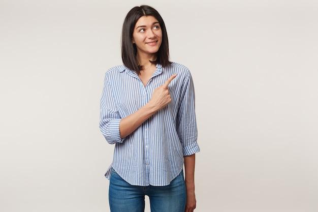 Szczęśliwa szczęśliwa zadowolona młoda brunetka patrzy z podekscytowaniem i uśmiechem w prawy górny róg i wskazuje tam palcem wskazującym na miejsce, ubrana w koszulę, odizolowana