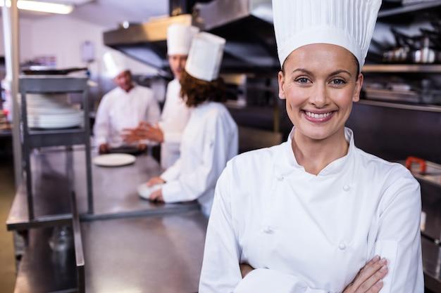 Szczęśliwa szef kuchni pozycja w handlowej kuchni w restauraci