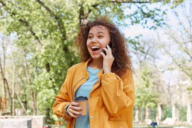 Szczęśliwa szeroko uśmiechnięta dziewczyna z kręconymi włosami, ubrana w żółtą kurtkę, pijąca kawę, ciesząca się pogodą w parku, rozmawiająca przez telefon z przyjacielem i śmiejąca się z zabawnych dowcipów.