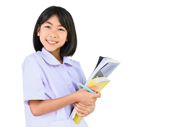 Szczęśliwa szkolna dziewczyna, azjatyccy dzieci trzyma stos książek spojrzenia przy kamerą i uśmiech szczęśliwą twarz na bielu