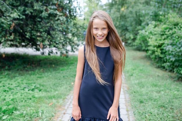 Szczęśliwa szkolna dziewczyna pozuje w szkolnych ourdoors