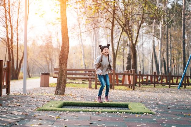 Szczęśliwa szkolna dziewczyna skacze na małej trampolinie w parku