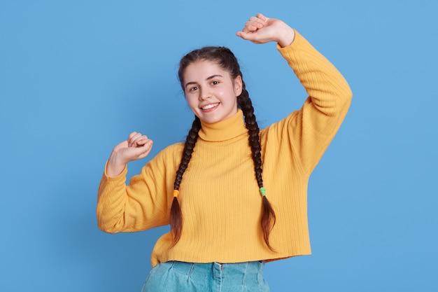Szczęśliwa tańcząca kobieta o ciemnych włosach i warkoczykach, odizolowana na niebieskiej ścianie, będąc w dobrym nastroju, patrząc prosto z przodu z zębatym uśmiechem