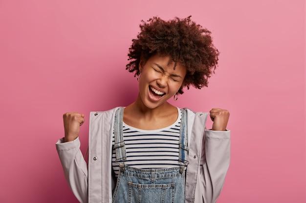 Szczęśliwa triumfująca kobieta wykrzykuje z radości brawo, zaciska pięści, raduje się z najlepszych wyników, ma wielki triumf i zwycięstwo, przechyla głowę, ubrana w modne ciuchy, szczęśliwa z awansu w karierze