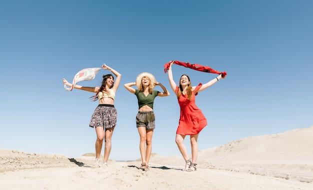 Szczęśliwa trzy kobiety ma zabawę chodzi na plaży. młodzi ludzie na wakacyjnych wakacjach cieszą się wolnością