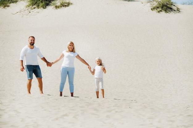 Szczęśliwa trzyosobowa rodzina na wydmach morza bałtyckiego w pobliżu miasta nida.wycieczka rodzinna do europe.lithuania.
