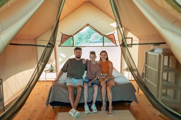 Szczęśliwa trzyosobowa rodzina siedzi na dużym łóżku w domu glampingowym